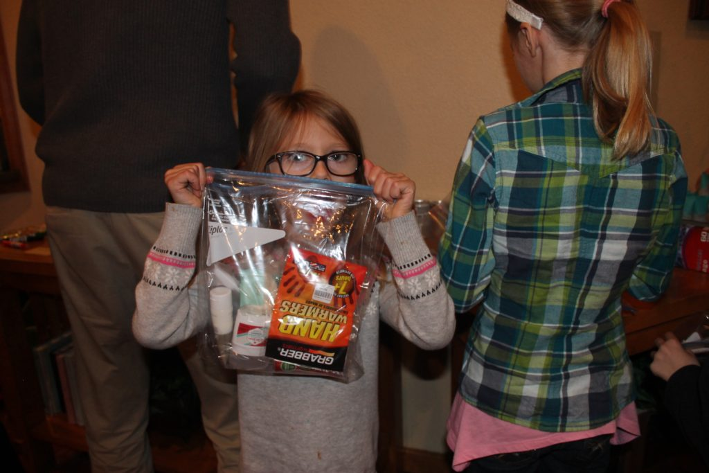 My lovely little niece with one of the care packages we put together. Each had toiletries, granola bar, V-8, pair of socks, beef jerky, hand warmers and a $5 McDonalds gift card.